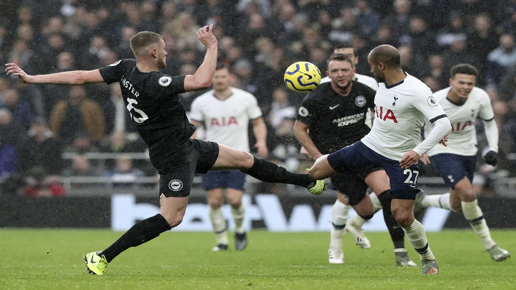 Tottenham's Lucas Moura fights for the ball with Brighton's Adam Webster, left, during the English Premier League football match at the Tottenham Hotspur Stadium in London, England, Thursday, Dec. 26, 2019. (AP Photo/Petros Karadjias.