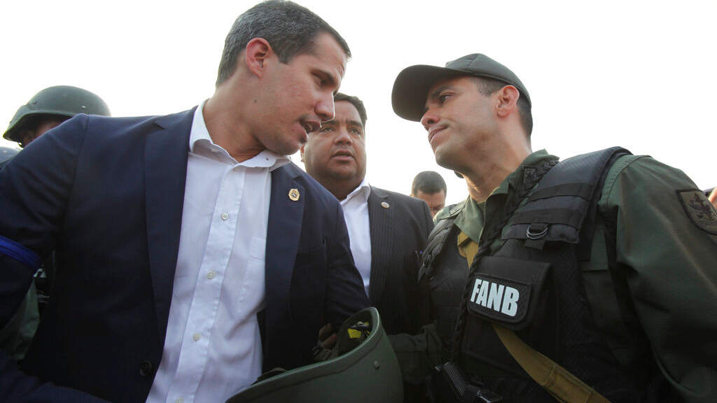 FILE - In this April 30, 2019 file photo, Venezuela's opposition leader and self-proclaimed president Juan Guaido talks to an Army officer outside La Carlota air base in Caracas, Venezuela. Guaido took to the streets with a small contingent of armed soldiers and detained activist Leopoldo Lopez calling for a military uprising. (AP Photo/Boris Vergara, File)