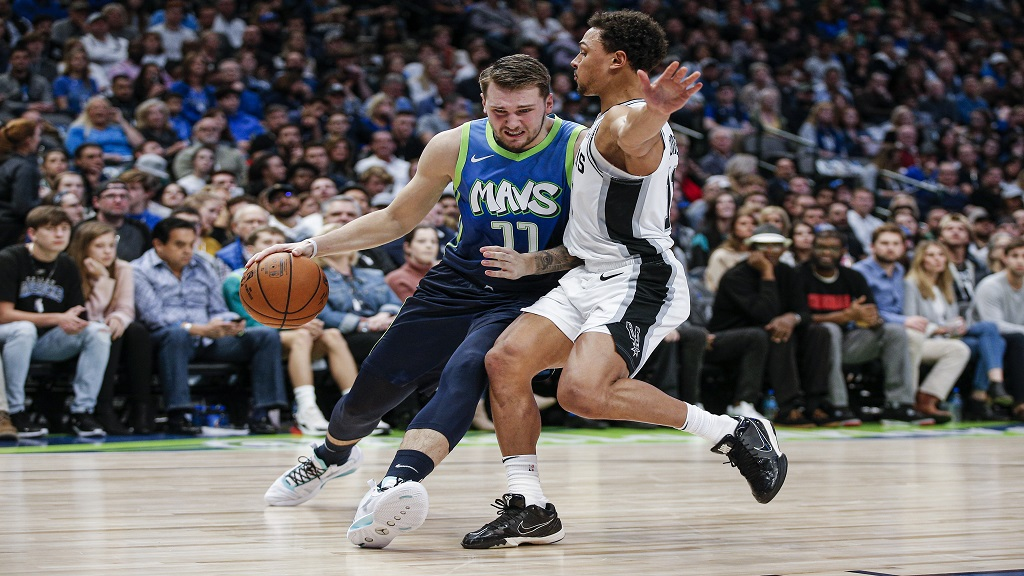 Dallas Mavericks forward Luka Doncic (77) battles San Antonio Spurs guard Bryn Forbes (11) for space during the first half of an NBA basketball game, Thursday, Dec. 26, 2019, in Dallas. (AP Photo/Brandon Wade).