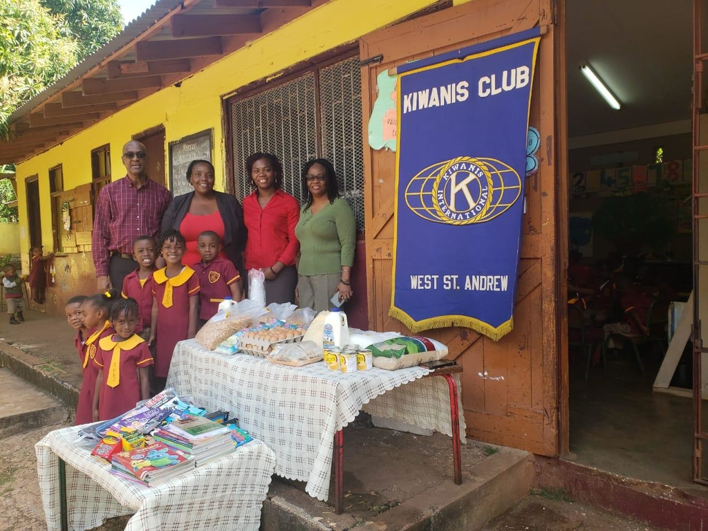 From left: KCWSA's Distinguished President James McNish, Principal of the Red hills Basic School Charmaine Williams, KCWSA's PR Chairman Marshalyn Rose and director of the club's Young Priority One committee, Ionie  Henry,  along with some of the children, stand beside the donated items.