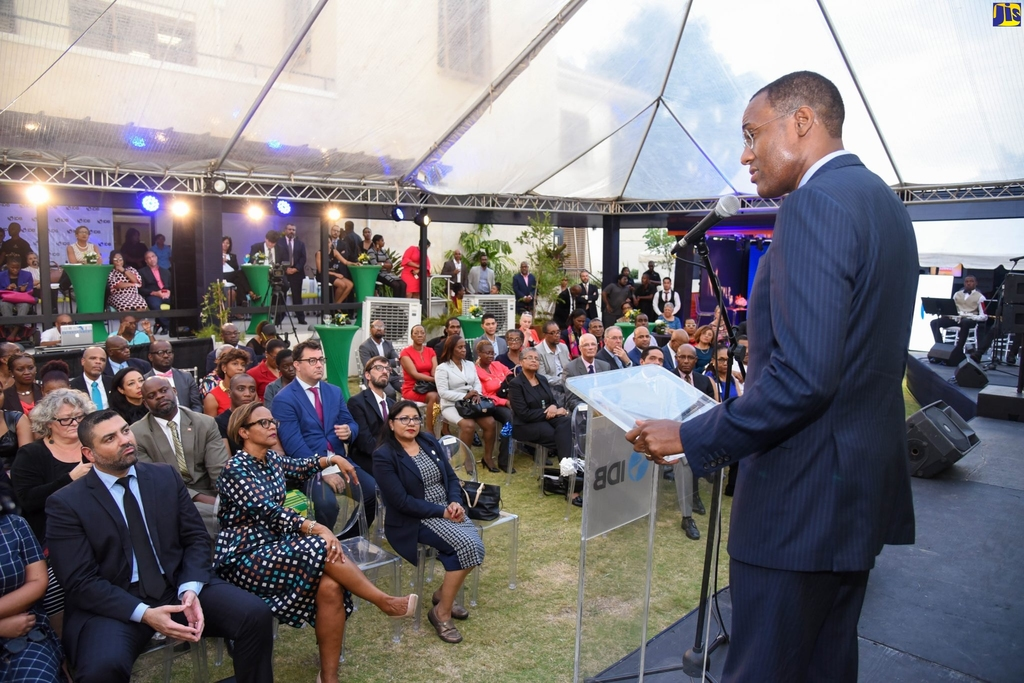 Minister of Finance and the Public Service, Dr Nigel Clarke (at podium), addresses attendees at the launch of the 50th anniversary of the Inter-American Development Bank's (IDB) operations in Jamaica, at its Montrose Road offices, in Kingston, on Thursday. (Photo: JIS)