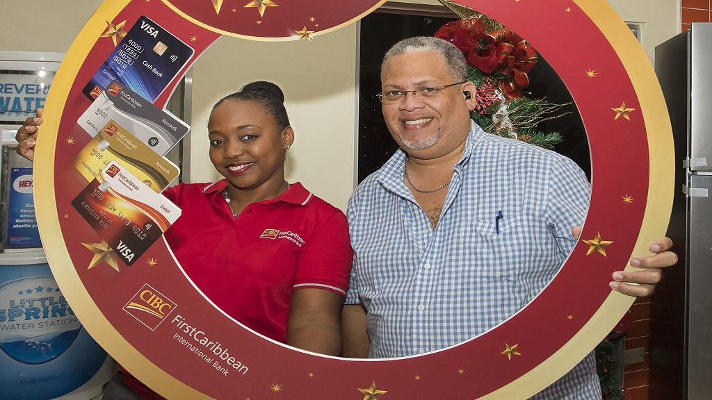 "Herbert Reid (right), one of the beneficiaries of the CIBC FirstCaribbean International Bank ""Jingle All the Way"" cards Christmas initiative, celebrates with Renee Whitehorne, Marketing Manager of the bank."