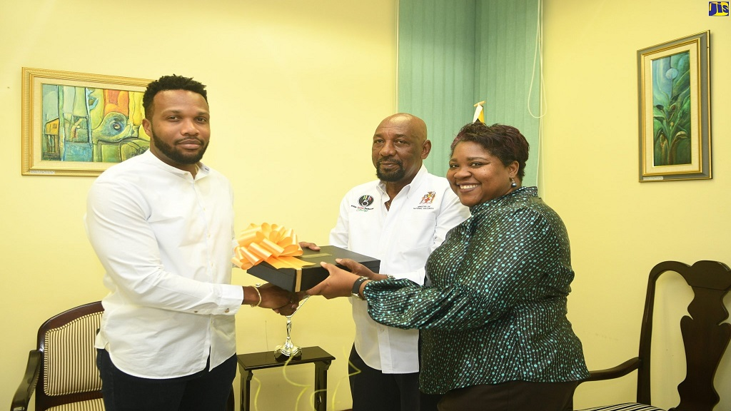 State Minister in the Ministry of National Security, Rudyard Spencer (centre), and Acting Chief Technical Director in the ministry, Shauna Trowers (right), present a box with a trophy to 'We Transform' ambassador and mentor, Jeffrey 'Agent Sasco' Campbell, at the ministry in New Kingston last week.