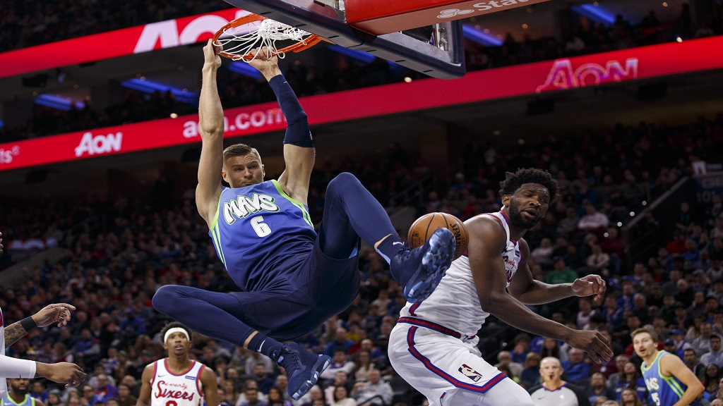 Dallas Mavericks' Kristaps Porzingis (6) dunks against Philadelphia 76ers'Joel Embiid, right, during the first half of an NBA basketball game, Friday, Dec. 20, 2019, in Philadelphia. (AP Photo/Chris Szagola).