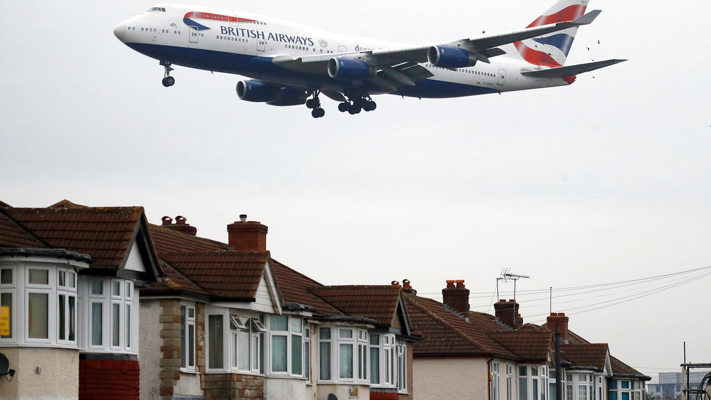 In this Tuesday, Oct. 25, 2016 file photo, a plane flies over nearby houses as it approaches for landing at Heathrow Airport in London. The British Cabinet on Tuesday June 5, 2018, is expected to approve the construction of a third runway at Heathrow Airport, and to put the long-running issue up for a parliamentary vote. (AP Photo/Frank Augstein, File)