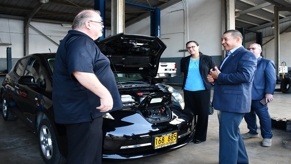 Minister Joey Hew speaks with Trainer Alan Nagal, Cayman Automotive. Looking on is Kristen Augustine, Energy Policy Coordinator in the Ministry of Commerce, Planning and Infrastructure
