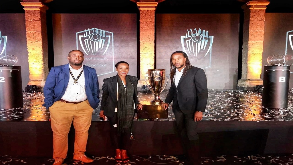 """Pictured with the Champions League Trophy at the live Draw in Mexico City (from right)  Ricardo """"Bibi"""" Gardner, Head Coach Portmore United FC; Paula Pinnock, Managing Director FYI Consultancy Group; and Rohn Rainford, Club Administrator, Portmore United FC."""
