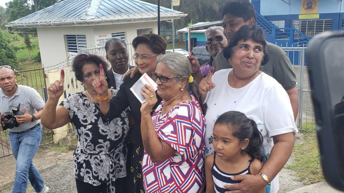 Opposition leader Kamla Persad-Bissessar poses for a photo with supporters after casting her ballot