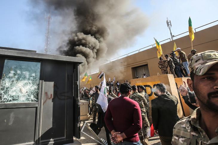 Des membres et partisans du Hachd al-Chaabi, coalition de paramilitaires dominée par des factions pro-Iran, incendient une tourelle devant l'ambassade des Etats-Unis à Bagdad le 31 décembre 2019 / AFP