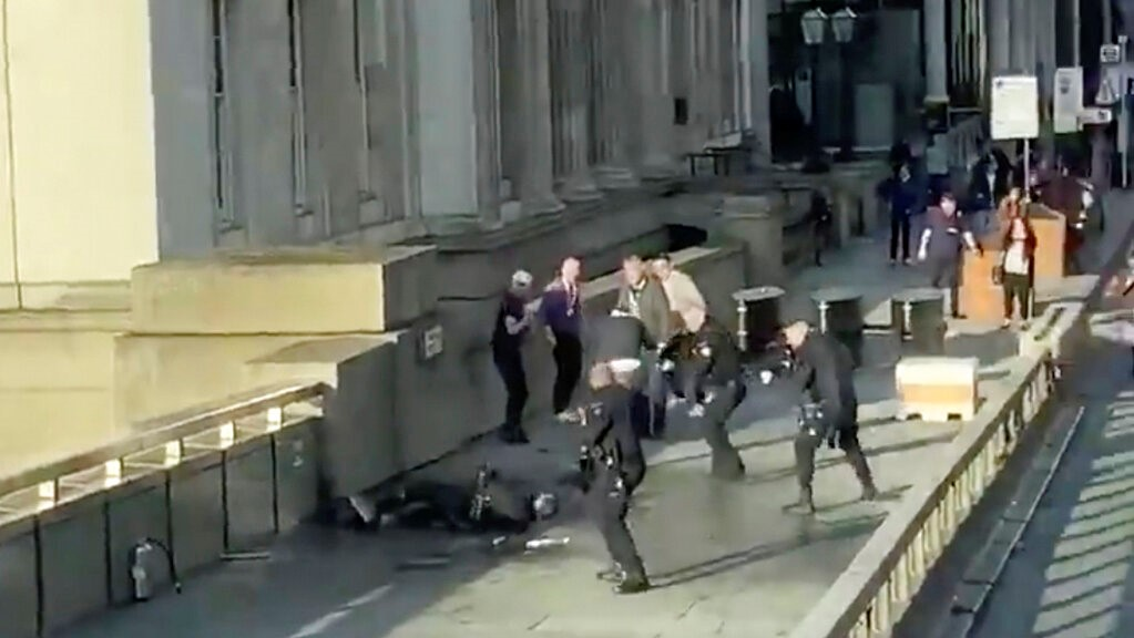 In this grab taken from video made available by @HLOBlog, a man is surrounded by police after an incident on London Bridge, in London, Friday, Nov. 29, 2019. (@HLOBlog via AP)