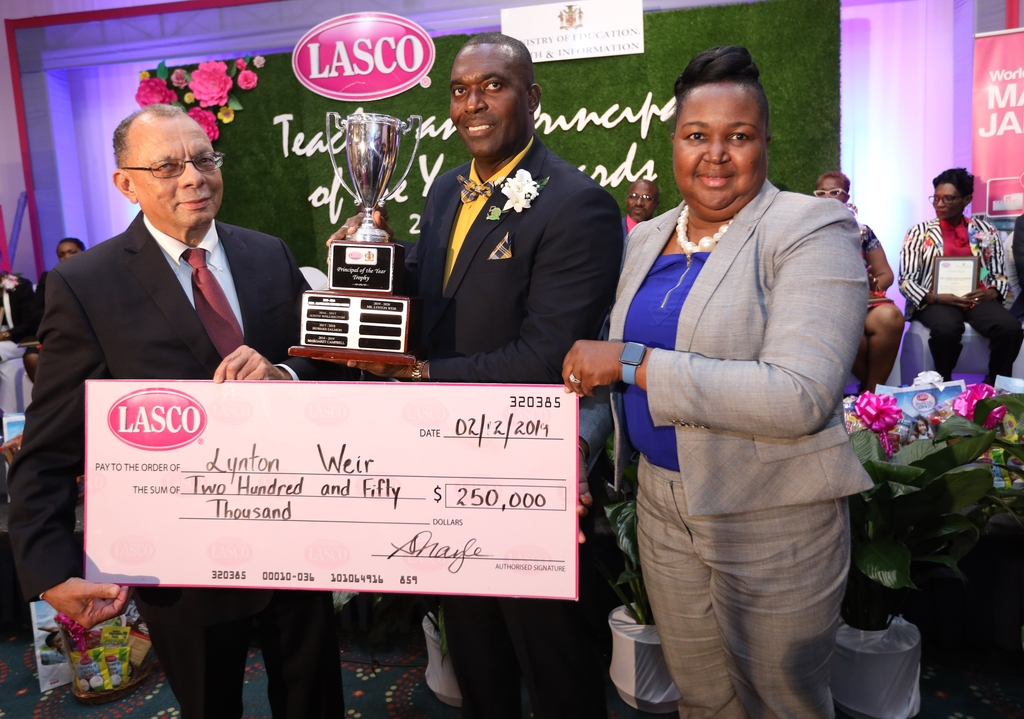 James Rawle (left), managing director of Lasco  Manufacturing Limited and Dr Grace McLean (right), acting permanent secretary of the Ministry of Education, Youth and Information (MoEYI) present Old Harbour High School's Lynton Weir with his winning trophy and cheque at the Lasco/MoEYI 2019-20 Principal of the Year awards luncheon.