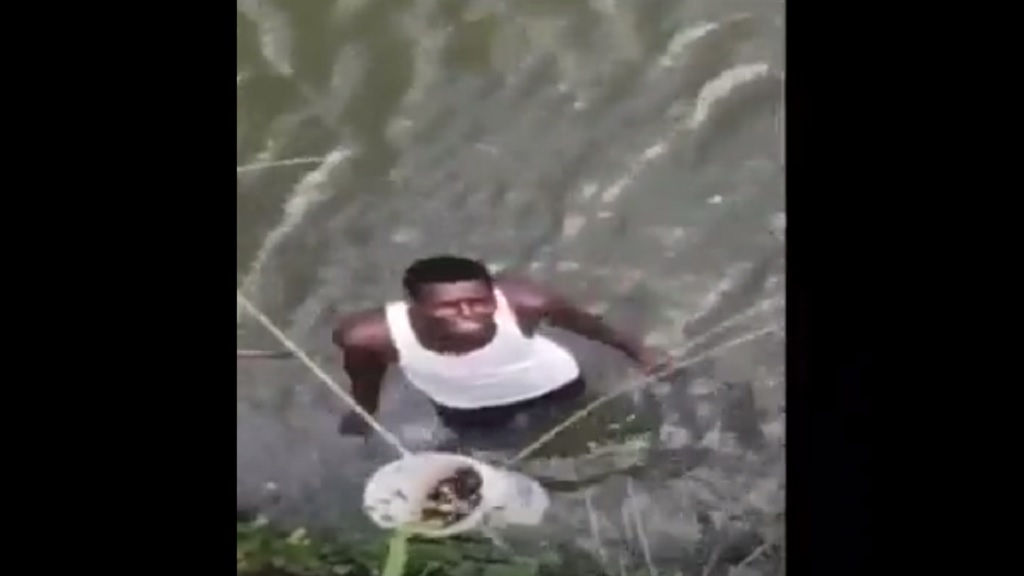A screen grab from a video of a group of young men removing bottles with names of persons therein that were found submerged in a river in St Mary.