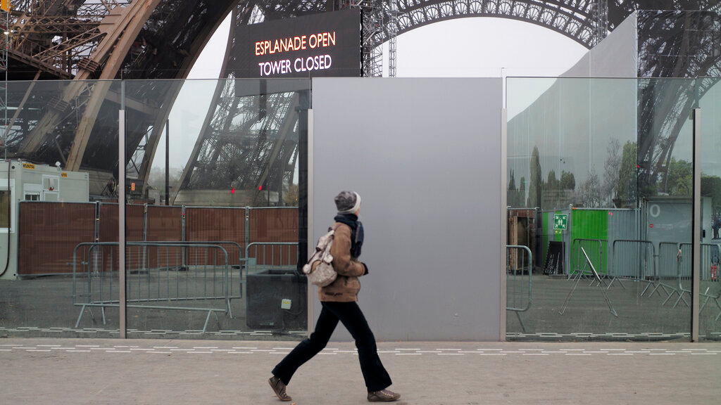 A woman walks past the closed Eiffel Tower in Paris, December 5, 2019. (AP Photo/Rafael Yaghobzadeh)