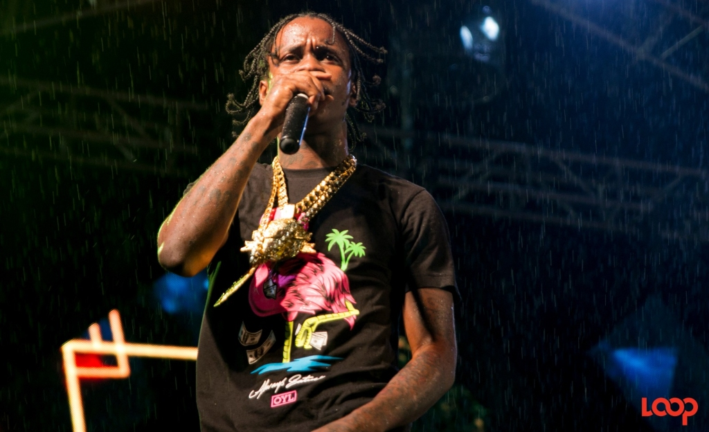 Prince Swanny performing in the rain at Hennessy Artistry Beach event in Barbados.