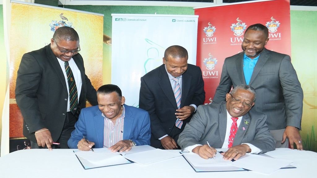 JCA President Wilford Heaven and UWI Mona Principal Dale Webber sign the MoU between the organisations at the Faculty of Sport at the UWI. Witnessing are (from left) JCA CEO Courtney Francis, UWI Mona Campus Lawyer Carl Lawrence and JCA's Business Development Manager Garth Williams.