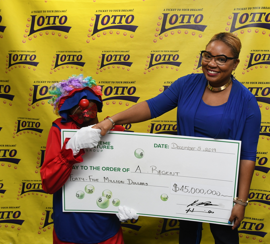 Supreme Ventures' Vice President, Marketing, Communication and Sponsorship, Gail Abrahams congratulates $45 million Lotto winner, A. Regent during the presentation on Thursday, December 6.