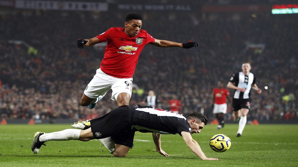 Manchester United's Anthony Martial, left, and Newcastle United's Fabian Schar battle for the ball during their English Premier League football match at Old Trafford, Manchester, England, Thursday, Dec. 26, 2019. (Martin Rickett/PA via AP).