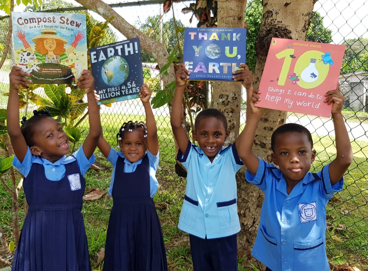 Students at Moneague Teachers' College Basic School in Jamaica share bright smiles after taking part in a reading session with environmental books.