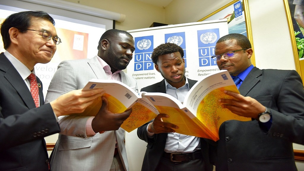 UNDP Programmes Specialist, Richard Kelly (right), discusses key findings of the United Nations 2019 Human Development Index Report with (from left) Resident Representative, Japan International Cooperation Agency (JICA), Takeshi Takano; Global Youth Leader and Development Policy Specialist, Tijani Christian; and UWI student and Model UN Delegate, Matthew McHayle.