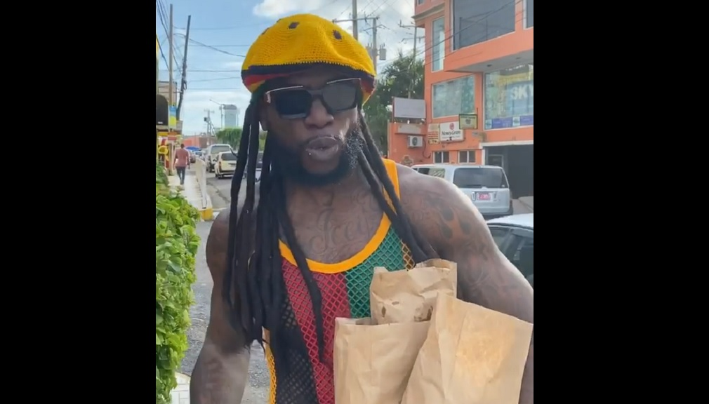 Screen grab of a video showing American rapper Gucci Mane, with a 'rastaman' wig, walking through the streets of a rural Jamaica town.