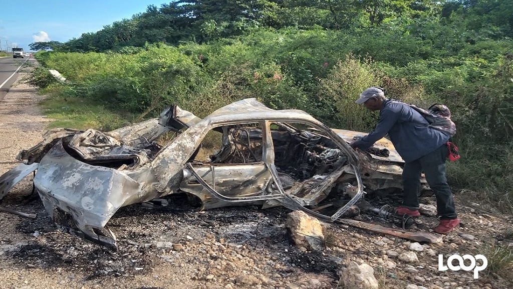 The remains of the car in which two persons perished after a collision on the Chesterfield Drive on the outskirts of Seaview Gardens in St Andrew on Monday.