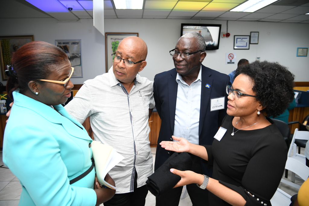 Claudine Allen (right), member ombudsman, at The Jamaica National Group makes a point to Michelle Hines (left), Business Relationship and Sales Manager at JN Bank at the inaugural meeting of the JN Circle, Spanish Town. Looking on are Councillor Norman Scott (second left), Mayor of Spanish Town and Major Effiom Whyte, member relations coordinator with JN Group.