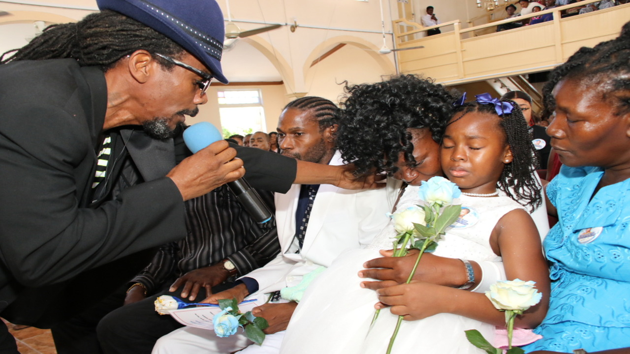 Singer Jah Formula offers words of comfort to Benamin Blair's mother, Japhene Campbell, and his sister, Seraphine Bair, at a funeral service  at the North Street Seventh Day Adventist Church in Kingston on Sunday.