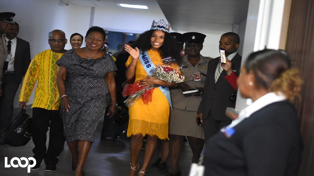 Miss World Toni-Ann Singh waves as she arrives inside the Norman Manley International Airport on Friday. Culture, Gender, Entertainment and Sport Minister, Olivia Grange is pictured beside her. (Photos: Marlon Reid)