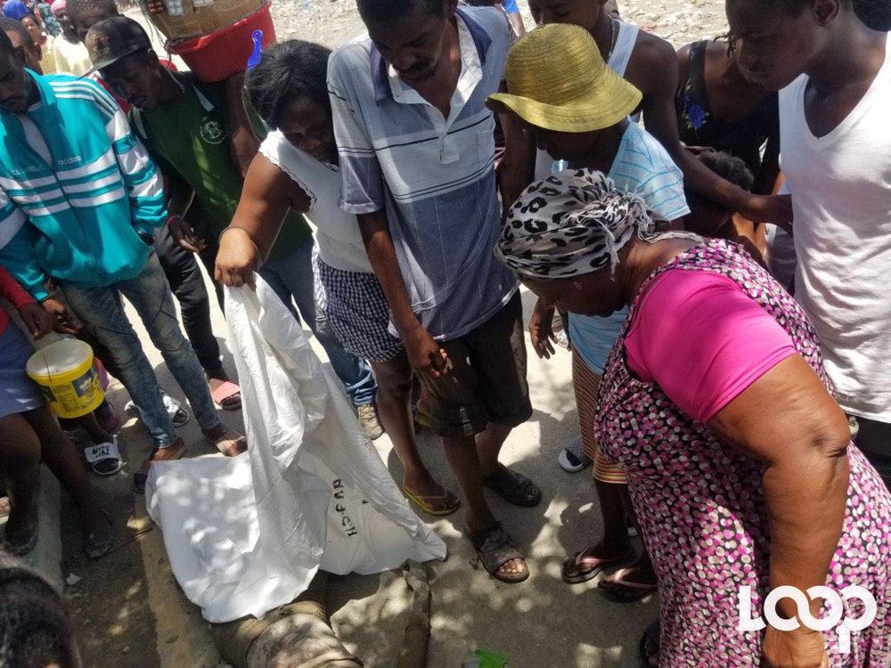 Photo illustrant une foule autour d'un cadavre retrouvé en juin à Cité Soleil après les intempéries.