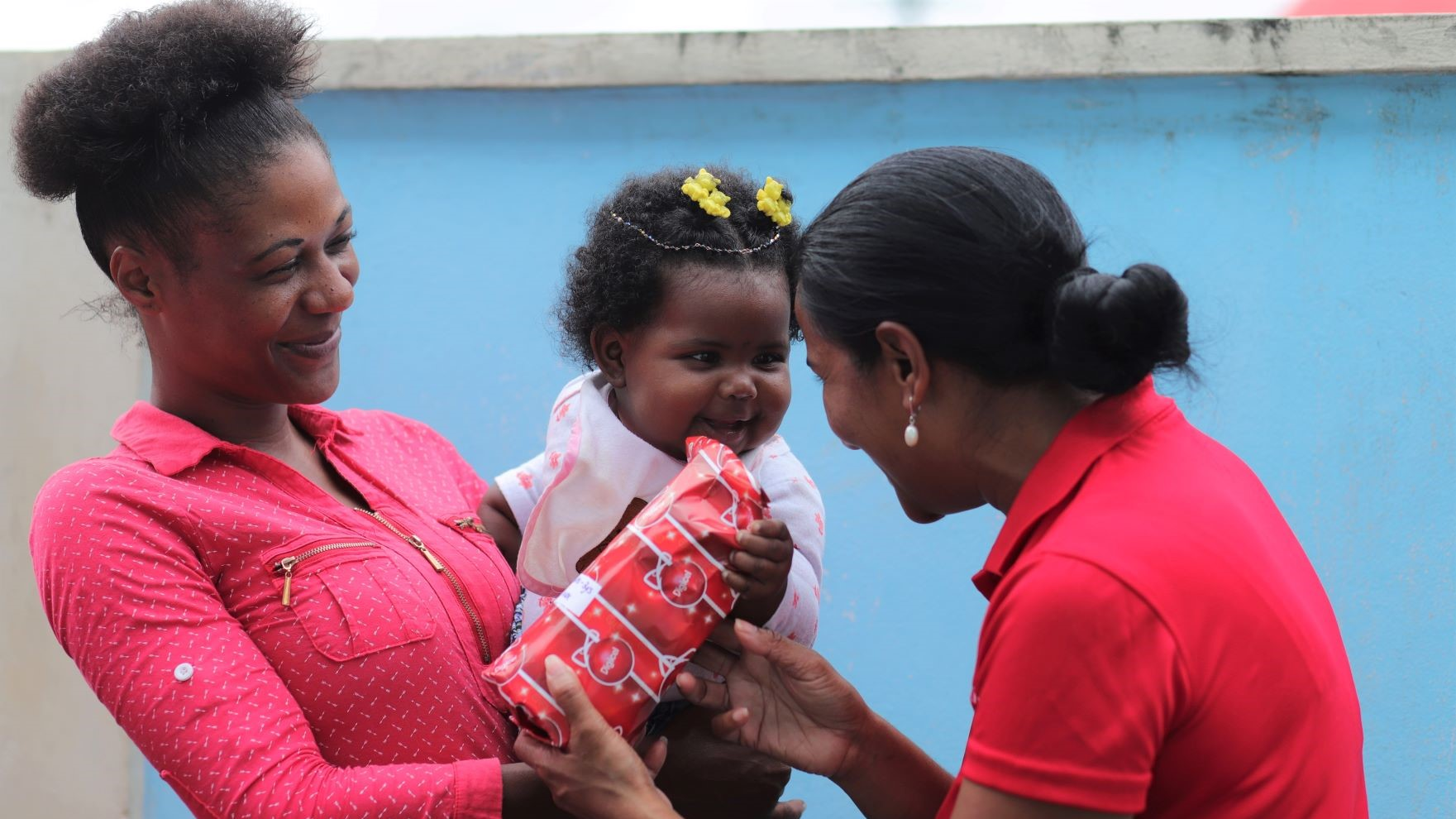 Diana Mathura-Hobson, Digicel Foundation Project Coordinator (right) captured in a cherished moment with this little cutie as she presents her with a Christmas gift during the Martin's Taxi Service annual Christmas party.