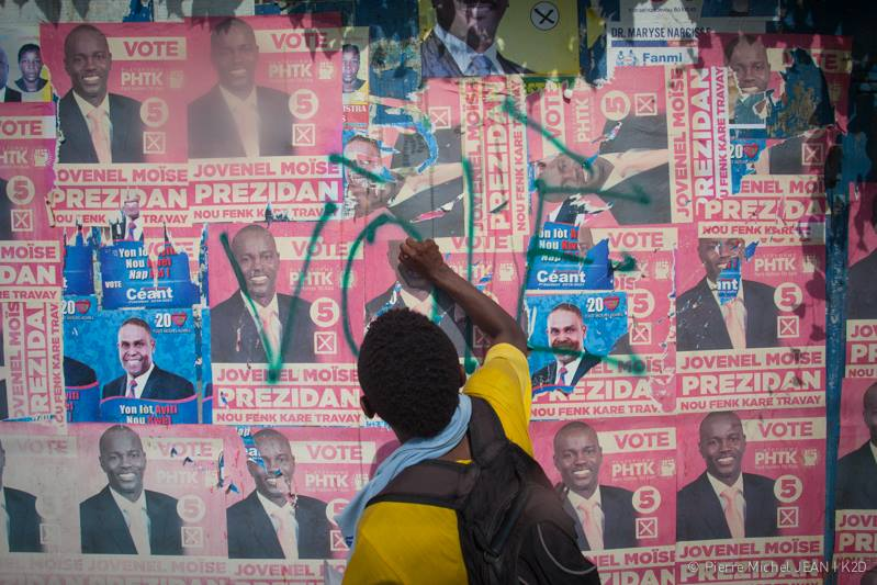 Un citoyen haïtien en train d'arracher les affiches électorales du candidat Jovenel Moïse  lors des élections haïtiennes de 2015-2016. Crédit photo: Pierre Michel Jean