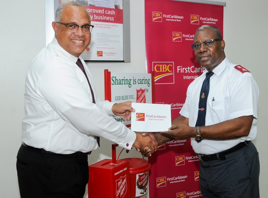 CIBC FirstCaribbean's Managing Director, Mark St. Hill, left, presenting Divisional Commander Major Darrell Wilkinson with the donation.