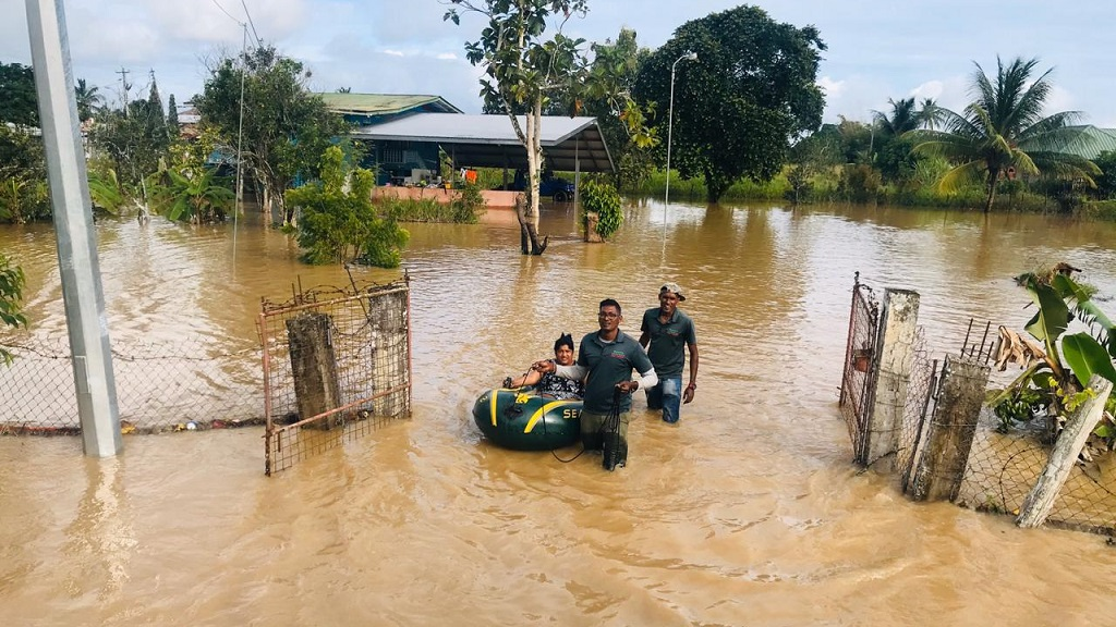 Photo: Navin and Ravi Kalpoo rescue a resident from flood waters. The Kalpoo Brothers have been called 'flood heroes' for their dedication and work in helping those affected by flooding in 2018 and 2019.