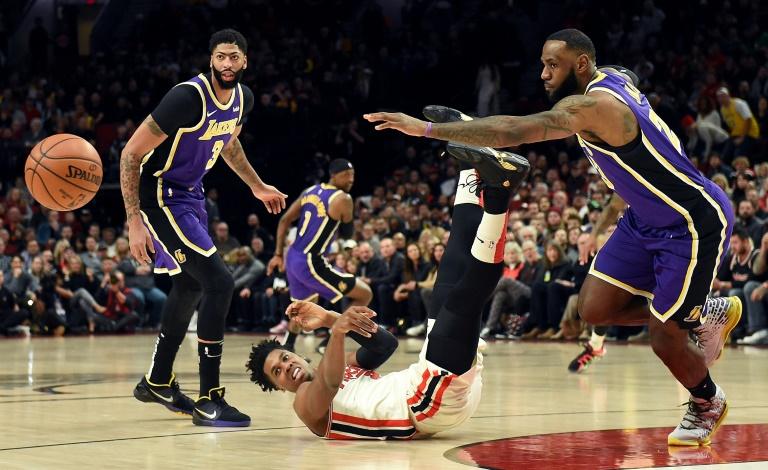 LeBron James (d) et Anthony Davis (g) des Los Angeles Lakers à la lutte avec Hassan Whiteside (au sol) des Portland Trail Blazers, en NBA, le 6 décembre 2019 à Portland