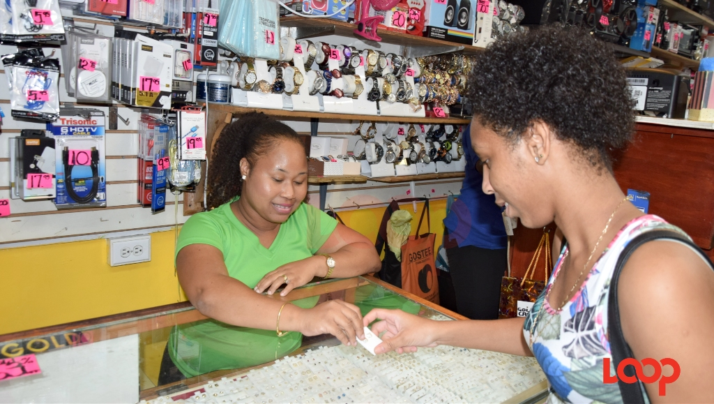 Dacia Moore, Store Manager of Tropicana Jewellers shows a female customer some of the studs on display.