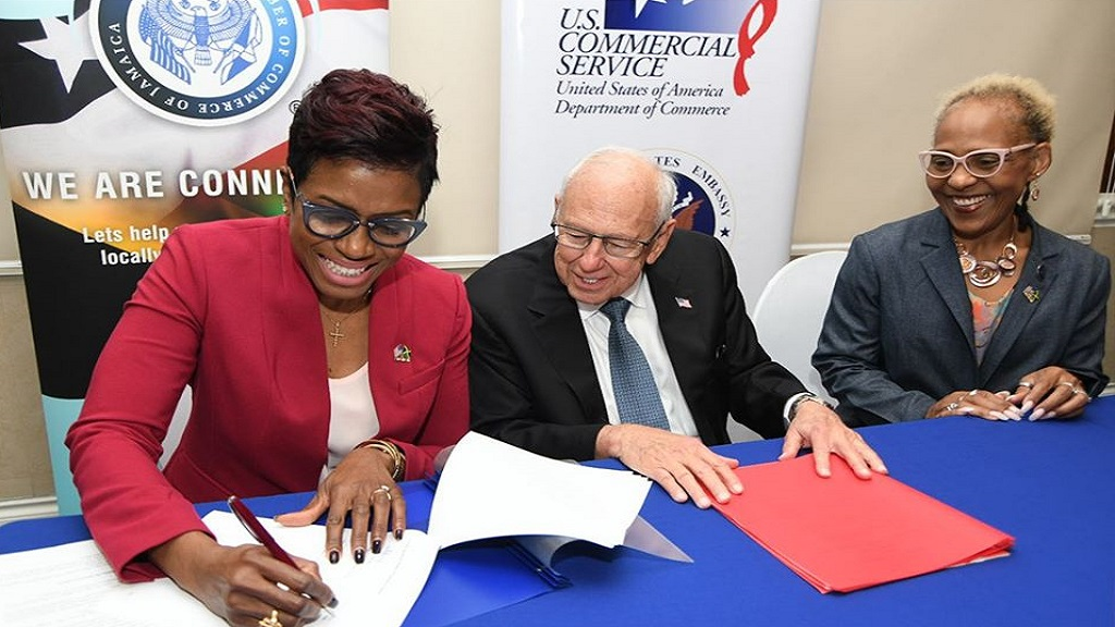 US Ambassador to Jamaica  Donald Tapia (centre) looks on as President of the American Chamber of Commerce of Jamaica (AMCHAM Jamaica) Ann-Dawn Young Sang (left) sign the MoU. Sharing in the moment is Gillian Haughton CEO of Amcham Jamaica (right).