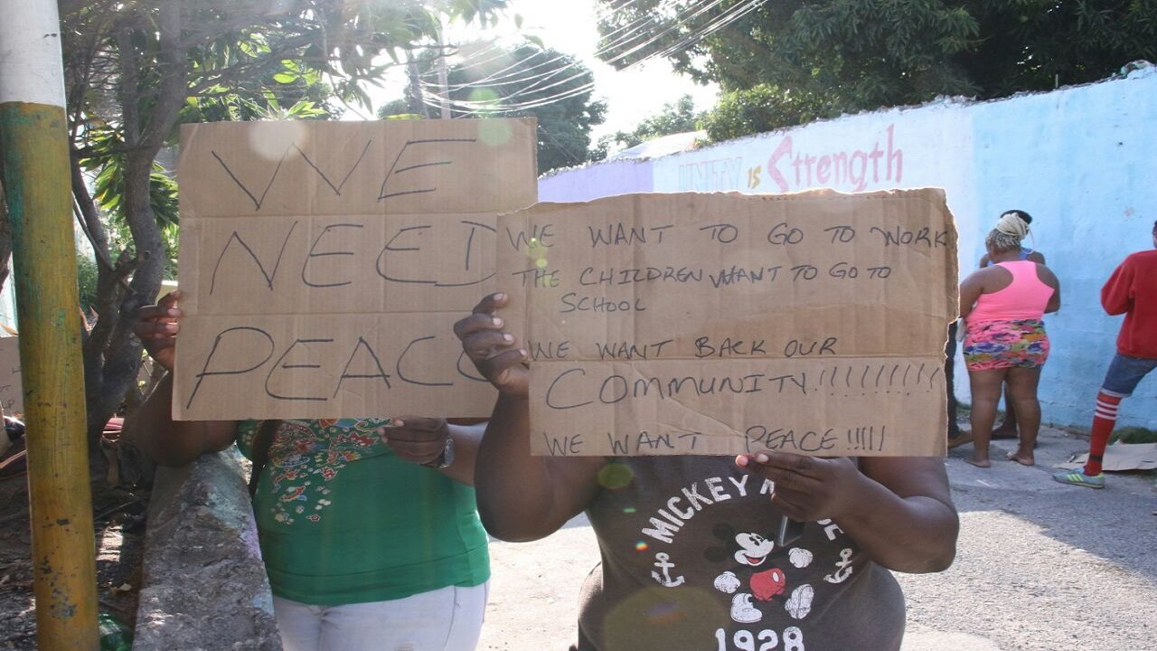 Placard-bearing Mountain View residents appeal for peace in a previous flare up of violence in the area. (File photo)