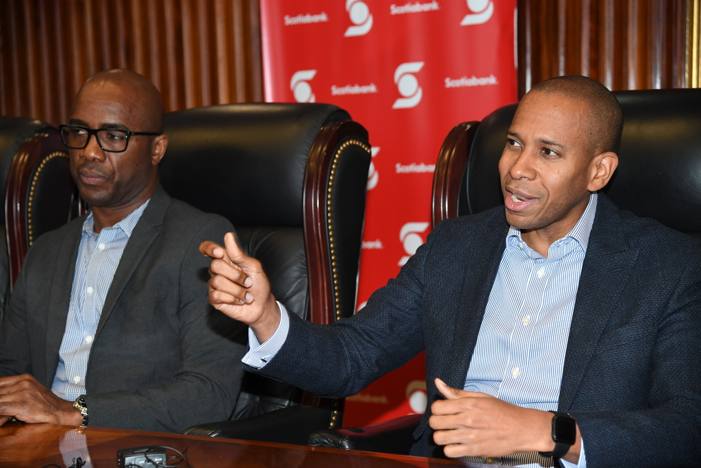 President and CEO of Scotia Group Jamaica David Noel (right) makes a point at a media briefing on Friday. Listening on is Adrian Stokes 