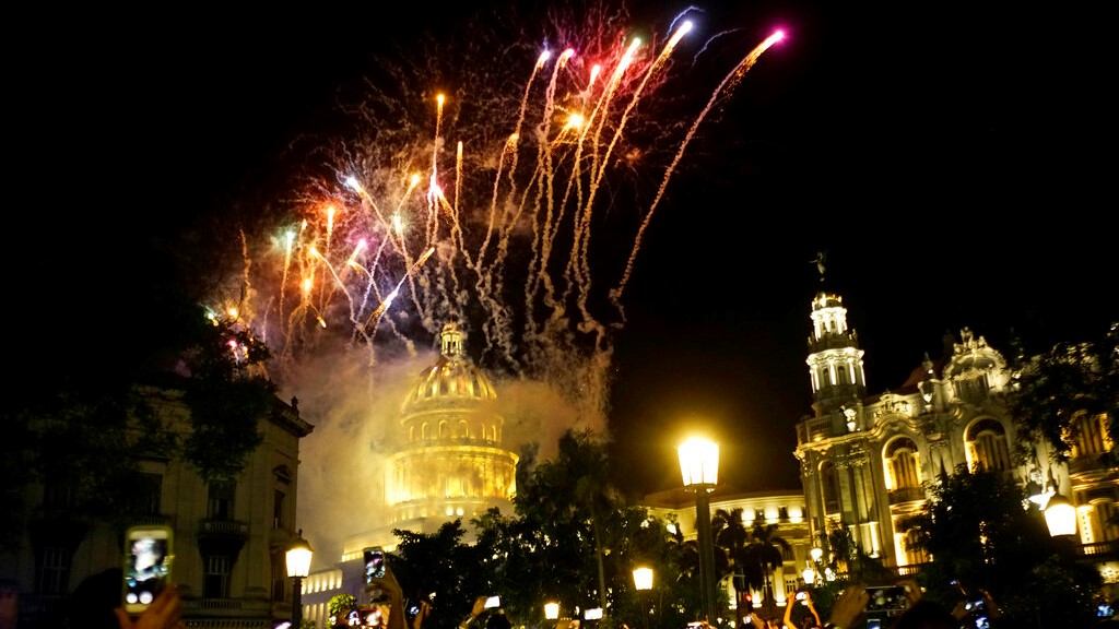 People take pictures of the fireworks at the Capitol during a gala as part of the celebration of the 500 years of the city in Havana, Cuba - Saturday November 16, 2019. (AP Photo/Ramon Espinosa)