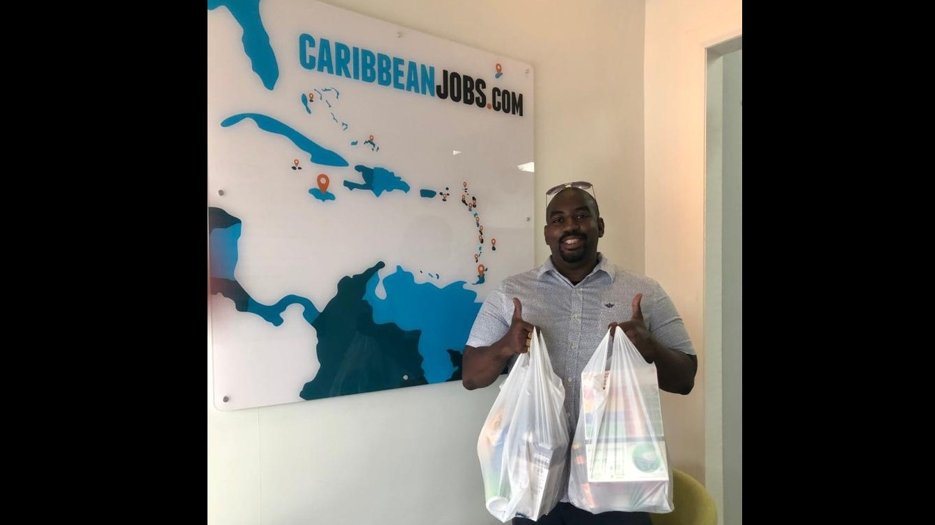 Garth Francis, Business Development Manager, CaribbeanJobs with donations made in their donation drive to assist the Society of St. Vincent De Paul