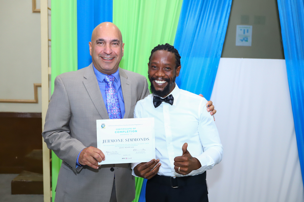 President and CEO of Sagicor Group Jamaica, Christopher Zacca, (left), congratulates Jermone Simmonds, valedictorian for the ACTS/CSJP 2019 cohort on his achievement.