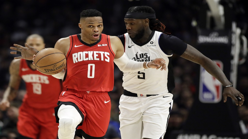Houston Rockets' Russell Westbrook (0) dribbles past Los Angeles Clippers' Montrezl Harrell during the second half of an NBA basketball game Thursday, Dec. 19, 2019, in Los Angeles. (AP Photo/Marcio Jose Sanchez).