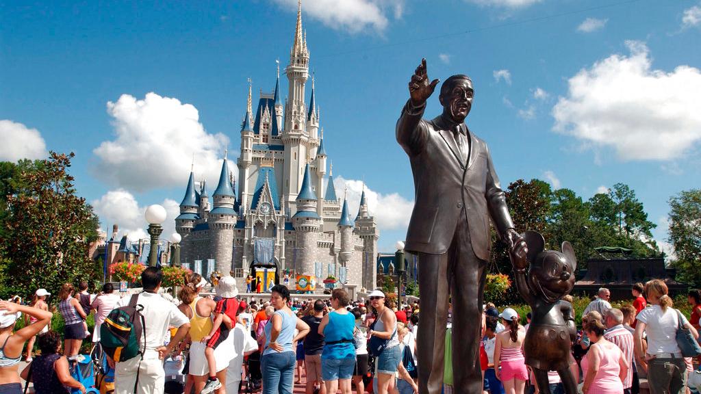 In this Sept. 2, 2004, file photo, tourists crowd around Cinderella's Castle to watch a performance at Walt Disney World's Magic Kingdom in Lake Buena Vista, Fla. (AP Photo/Phelan M. Ebenhack, File)