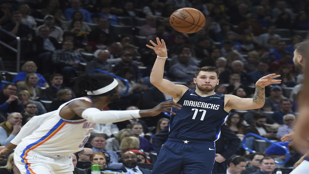 Dallas Mavericks guard Luka Doncic (77) passes the ball over Oklahoma City Thunder forward Nerlens Noel (9) in the first half of an NBA basketball game, Monday, Jan. 27, 2020, in Oklahoma City. (AP Photo/Kyle Phillips).