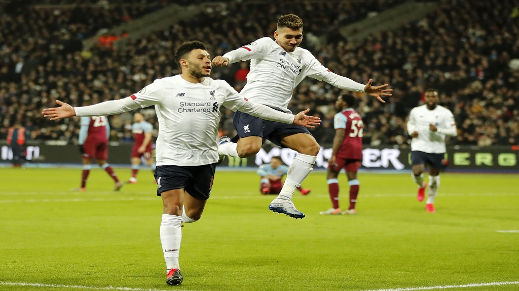 Liverpool's Alex Oxlade-Chamberlain, left, celebrates with Roberto Firmino after scoring his side's second goal during the English Premier League football match against West Ham Utd at the London Stadium in London, Wednesday, Jan. 29, 2020. (AP Photo/Frank Augstein).