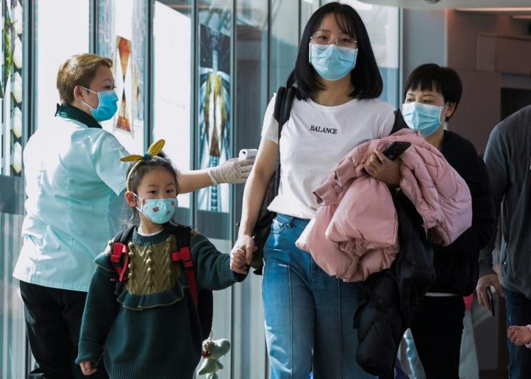 Une employée contrôle la température des passagers en provenance de Chine à leur arrivée à l'aéroport de Singapour, le 22 janvier 2020. AFP / ROSLAN RAHMAN