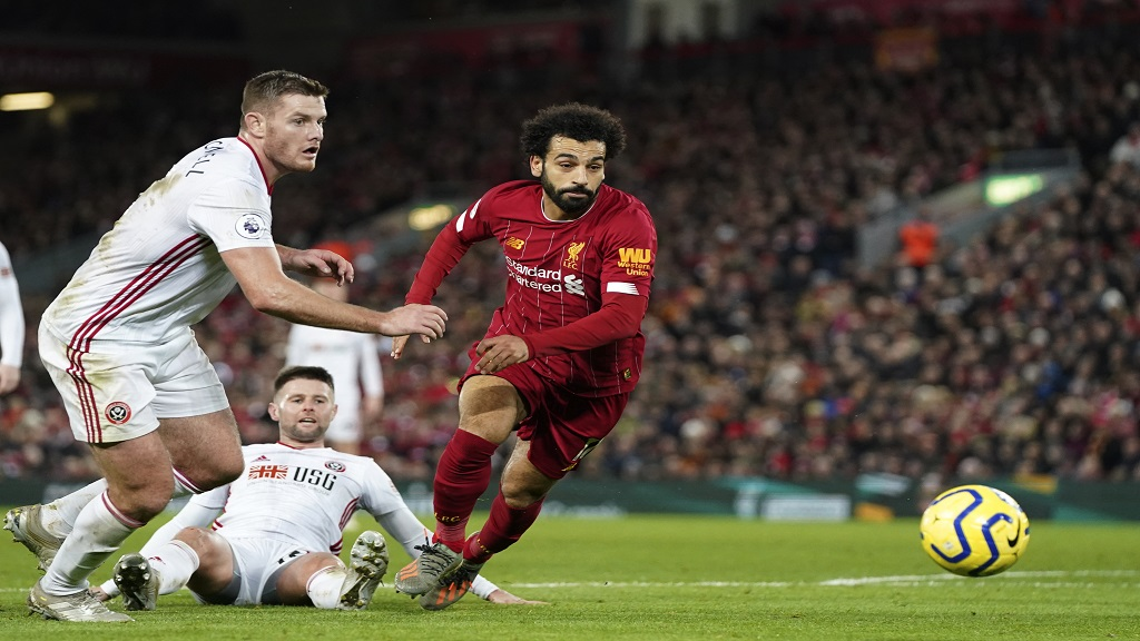 Sheffield United's Jack O'Connell, left, and Liverpool's Mohamed Salah run for the ball during their English Premier League football match at Anfield Stadium, Liverpool, England, Thursday, Jan. 2, 2020. (AP Photo/Jon Super).