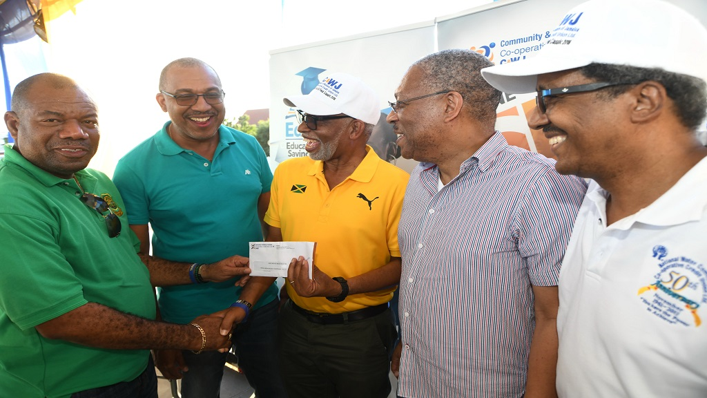 Condell Stephenson (3rd left), President of Community & Workers of Jamaica Co-operative Credit Union (C&WJ) presents a letter of commitment of $1.5m sponsorship towards the McKEnley & Wint Track & Field Classic 2021 to Albert Corcho (left), Principal of Calabar , while David Miller (2nd left) co-ordinator of the classic and Michael Dunn (right), director of C&WJ look on.
