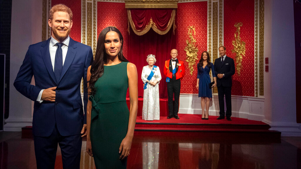 The figures of Britain's Prince Harry and Meghan, Duchess of Sussex, left, are moved from their original positions next to Queen Elizabeth II, Prince Philip and Prince William and Kate, Duchess of Cambridge, at Madame Tussauds in London, Thursday January 9, 2020. (Victoria Jones/PA via AP)