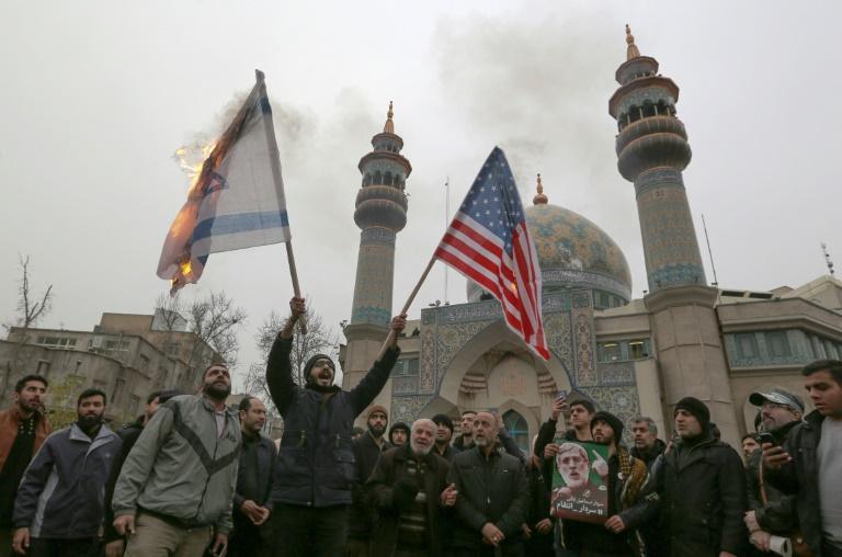 Des Iraniens brûlent les drapeaux israélien et américain le 5 janvier 2020 à Téhéran lors d'une manifestation contre l'assassinat du général Qassem Soleimani, tué dans une frappe américaine en Irak